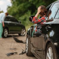 Scène d'accident : Femme dans sa voiture accidentée se tenant la tête ett homme au loin, sur la route, constatant les dégâts sur son véhicule.