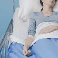 Femme avec la main sur son ventre allongée sur un lit dans un hôpital.